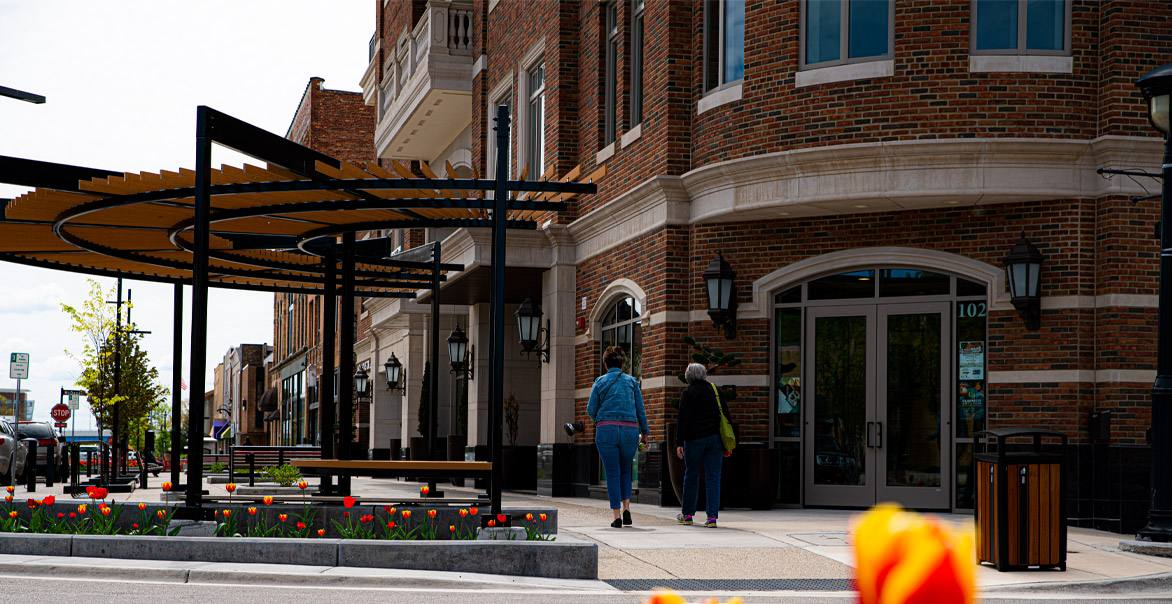 A street corner with an outdoor pergola and retail shops